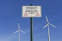 Wind turbines and warning sign. Two wind turbines and a warning sign Royalty Free Stock Images