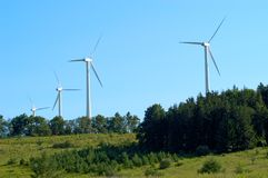Wind turbines at wind farm. Line of wind turbines in green field in countryside against blue sky.  Located in wind farm in Western New York State Royalty Free Stock Image