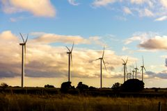 Wind turbines in a wind power plant at sunset stock images