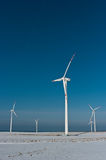 Wind turbines in winter. Several wind turbines in a white field, against a blue sky. The shadow of a wind turbine seen in the foreground Royalty Free Stock Photos