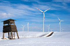 Wind turbines in the winter. Wind turbines in the snow behind a dilapidated hunting seat stock images