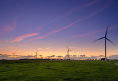Wind turbines at work. Evening falls bit the wind turbines keep doing their job Stock Photos