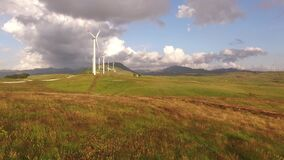 Wind turbines in a yellow field with blue skies and white clouds.