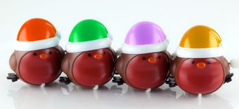 Wind up robins with colorful hats. Four little windup plastic robin toys with colorful hats Royalty Free Stock Photography