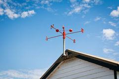 Wind vane. Red wind vane at the roof top royalty free stock photo