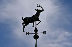Weather vane of a deer silhouetted in the sky. A wind vane with an antlered deer is silhouetted n the sky royalty free stock image