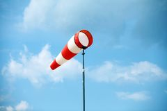 Wind vane. A red wind vane against a blue cloudy sky stock images