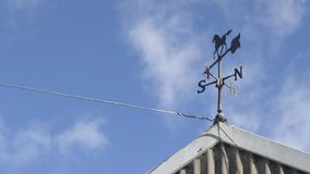 A wind vane on a stable`s roof. A steady zoomed in shot of a wind vane from a stable`s roof stock video footage