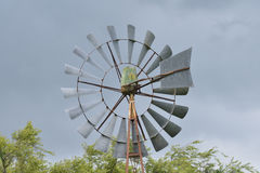 Wind Water Pump. Close up of an old wind water pump against a dark stormy sky stock image
