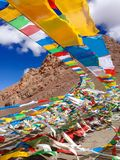 Wind wavering Buddhist Tibetan Chinese prayer flags with Sanskrit calligraphy written decorating mountain valley in Tibet, China Stock Photography