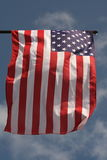 Wind from the west. American flag on the blue sky background, sunshine and wind Stock Photo