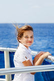 Windblown boat ride. Young girl looks out from a boat rail Stock Image