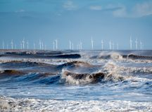 Windblown vågor som bryter på kusten med en vindlantgård på horisonten fotografering för bildbyråer