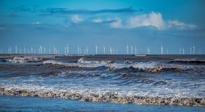 Windblown Wellen, die auf das Ufer mit einem Windpark auf dem Horizont brechen lizenzfreie stockfotografie