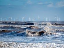 Windblown Wellen, die auf das Ufer mit einem Windpark auf dem Horizont brechen stockbild