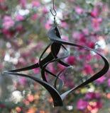 Windchime tegen roze bloemenachtergrond Stock Afbeeldingen