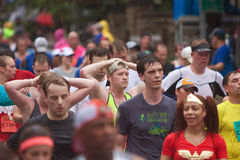 Winded Runners Recover After Finishing Atlanta Peachtree Road Race. Atlanta, GA, USA - July 4, 2015:  Runners put their hands on their heads to catch their Royalty Free Stock Image