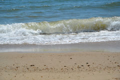 Winden in der Welle durch den Strand Lizenzfreie Stockfotografie