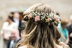 Winden Sie mit blonder Braut der hinteren Ansicht der Blumen mit einer Kükenfrisur Lizenzfreie Stockfotografie
