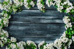 Winden Sie Rahmen mit weißen Blumen und den Niederlassungen, die auf altem Retro- Holztischhintergrund lokalisiert werden Lizenzfreie Stockbilder