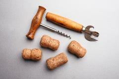 Winden Sie sich, Flaschenöffner und Weinkorken auf einem grauen Hintergrund Lizenzfreie Stockfotos