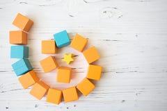 Winden Sie sich von den hölzernen Würfeln des orange und blauen Spielzeugs auf weißem hölzernem Hintergrund Stockbilder