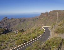 Windende asfalt weg aan dorp Masca met groene heuvels, scherpe bergpieken, van de overzeese achtergrond horizon de duidelijke bla Stock Fotografie