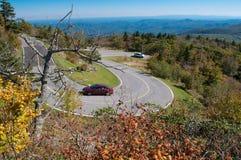 Windende kromme bij blauw randbrede rijweg met mooi aangelegd landschap stock foto