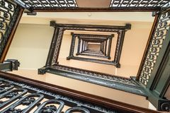Windende trap met houten leuning en ijzertraliewerk Stock Afbeeldingen