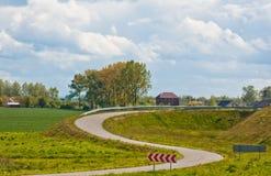 Windende weg naast het gebied op een achtergrond van heldere de zomerhemel overladen weg stock foto's