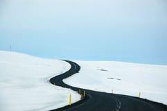 Windende weg, sneeuw, blauwe hemel, Dettifoss, IJsland Stock Fotografie
