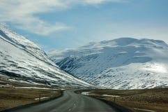 Windende weg, sneeuwberg, blauwe hemel, IJsland Royalty-vrije Stock Fotografie