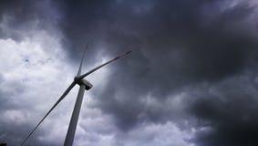 Windenergieeenheid die zich alleen met het glommy regenwolken omringen bevinden stock foto