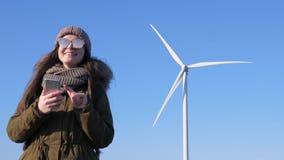 Windenergieinstallatie, jonge vrouw met gadget in handen die dichtbij schone duurzame energie veroorzaken stock video
