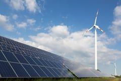 Windenergieturbine mit einigen Sonnenkollektoren für Stromerzeugung Lizenzfreie Stockfotos
