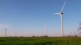 Windenergieturbinen auf Sonnenunterganghimmelhintergrund, Energiegeneratornatur freundlich grünes Gras und blauer Himmel stock video