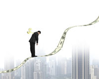 Winder on businessman's back standing on money trend with city Royalty Free Stock Images