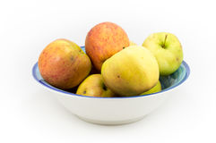Windfall apples grouped in a bowl on a white background. Royalty Free Stock Photography