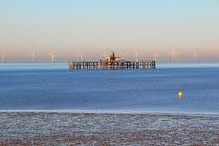 遗弃码头和windfarm 库存图片