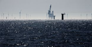 Windfarm construction on a sparkling sea stock photos