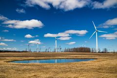 A windfarm beside a field royalty free stock photo
