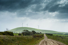 Windfarm on the hill. Windfarm perched on a hill with dark skies in the background Stock Photography