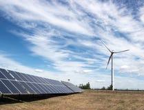 Windgenerator van elektriciteit van drie bladen en zonnepaneelbatterijen van fotocellen tegen een achtergrond van wolken en hemel stock afbeeldingen