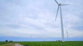 Windgenerators Panning van windturbines aan landelijke weg groene gebieden stock video