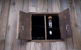 Windglockenspiele, die am hölzernen Fenster hängen stockfoto