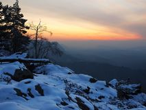 Windige Wintermorgenansicht zum Osten mit orange Sonnenaufgang. Tagesanbruch in den Felsen Lizenzfreie Stockbilder