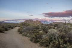 Winding Ariozna hiking trail with high clouds in Mcdowell Mountains. Winding hiking trail with high clouds in Mcdowell Mountains in Scottsdale, AZ royalty free stock photography