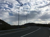 Winding asphalt road. Blue-gray cloudy sky, dark landscape. Vladivostok countrye Royalty Free Stock Photo
