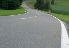 A winding asphalt road. Cross lines on road, Close up view of a road in curves stock image