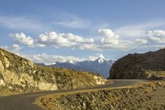 A winding asphalt road in the desert mountains against the snowy peaks under a blue sky with white clouds stock image